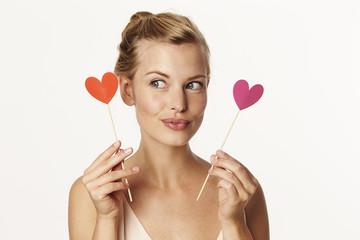 Beautiful woman choosing love heart, studio