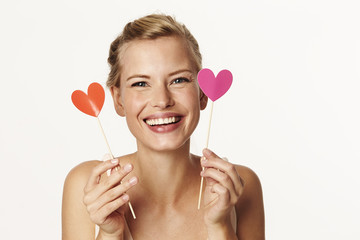Beautiful woman holding heart shapes in studio