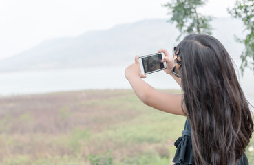 cute girl holding smartphone to taking selfie.