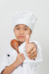 The young chef holds a spoon in his hand and thumbs up