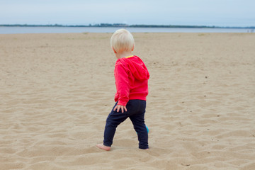 Blond baby walking on the beach