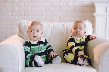 Two brother twins sitting. Two little kid boys watching at camera. Twins sitting together. People, children, friends and friendship concept
