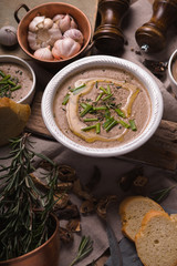 Mushroom cream soup on the rustic background vertical