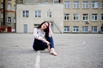 Young stylish teenage brunette girl on shirt, pants and high heels shoes, sitting on pavement and posed background school backyard. Street fashion model concept.