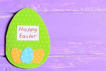 Happy Easter greeting card on purple wooden background with copy space for text. Paper greeting card made in form of egg with wishes Happy Easter. Easter background