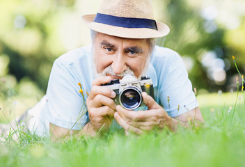 Senior man taking photographs outdoors, active lifestyle concept