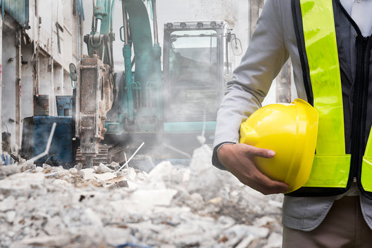 Engineer or Safety officer holding hard hat with the heavy equipment excavator demolition demolish machine in construction site.
