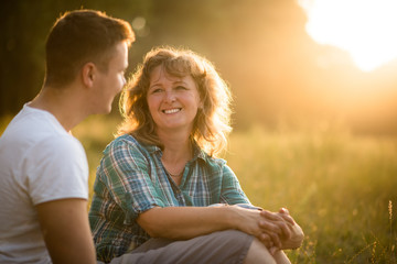 Beautiful senior woman and her adult smiling son sitting in park