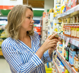 Young woman is choosing sauce in supermarket.