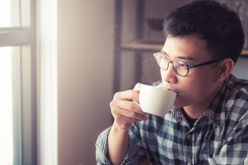 Asian young man drinking coffee in the cafe., How to lifestyle of young asian businessman in the weekend activity relaxing with the coffee. drinking concept.