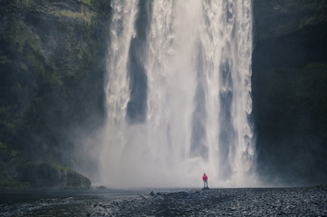 Southern Iceland. Man stands below the Skogafoss waterfall.