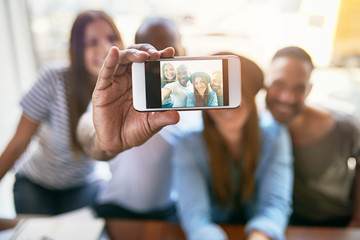 Group of friends taking selfie with phone