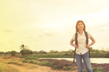 young traveler woman walking along country road.