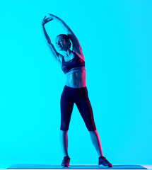 one mixed races woman exercsing stretching fitness exercices isolated on blue blackground