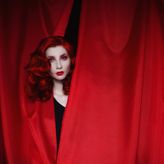 A woman with red curly hair in a black dress looking out of a red fabric. Red-haired girl with pale skin, a thin waist, blue eyes, a bright unusual appearance, red lips. Retro makeup. Theatre actress
