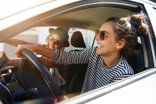 Two fun young women driving in a car
