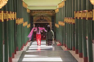 Rear view of people walking towards temple entrance