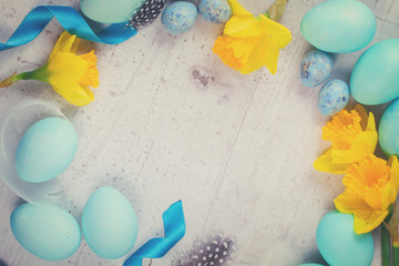 Easter frame with painted eggs and flowers on aged wooden desktop, retro toned