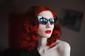 A woman with her red curly hair in a black dress and fox glasses on a dark background. Red-haired girl with pale skin, blue eyes, a bright unusual appearance, with red lips, looking out the window.