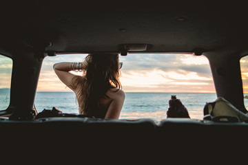 Rear view young woman looking out to sea from car interior