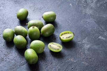 Baby kiwi or mini kiwi fruits on stone background. Closeup view