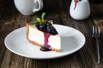 Piece of cheesecake with black currant and blueberry sauce on white plate on wooden table