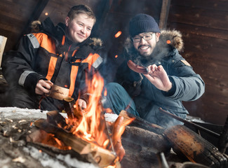 Two smiling men cooking sausages over campfire in log cabin