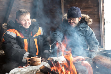 Two men cook over an open fire in log cabin