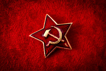 Old Soviet badge with the red star, a sickle and a hammer reminiscent of the cold war era worn by the soldiers of the red army on their hats, isolated on red velvet with a grungy aesthetic