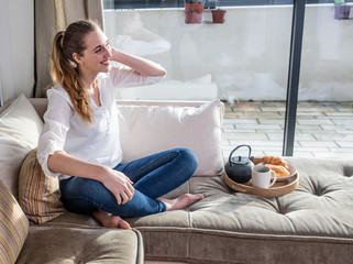thrilled beautiful girl enjoying sitting bare feet on comfortable sofa