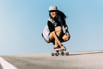 Beautiful skater woman riding on her longboard.