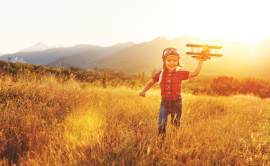 Child pilot aviator with airplane dreams of traveling in summer  at sunset. Fototapete
