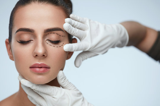 Closeup Of Beautician Hands Touching Young Female Patient Face