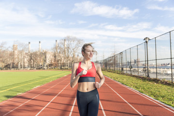 Young woman running on sports track, New York, USA