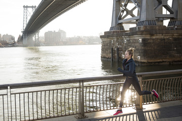 Athlete running on promenade by the East River in the city