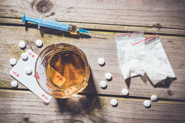Overhead shot of hard drugs and alcohol on wooden table. Addiction concept