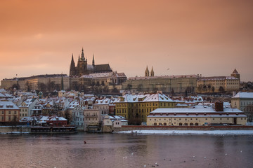View of Prague castle and buildings under the snow from Charles Bridge at sunset