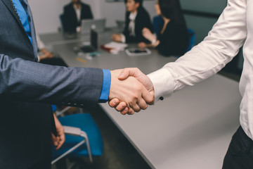 Two men handshaking in an office after successfull contract
