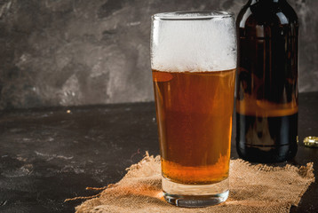 One open bottle of beer, a glass of beer, a foam. On a concrete background, copy space