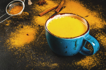 Traditional Indian drink turmeric milk is golden milk with cinnamon, cloves, pepper and turmeric. On a concrete table, with spices on the background. In mug, toned copy space