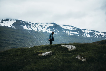 Man standing on cliff against snowcapped mountains