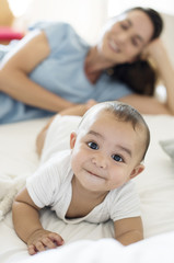 Mother looking at baby boy while lying on bed at home