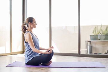 Side view of woman practicing yoga at home
