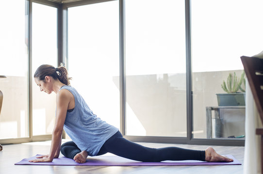 Side view of woman doing yoga on exercise mat at home