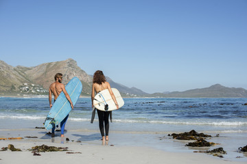 Rear view of friends carrying surfboard while walking at beach during sunny day