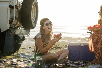 Happy female friends eating watermelon at beach against clear sky