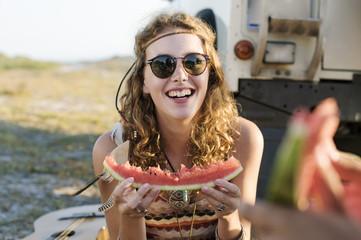 Happy woman eating watermelon at beach