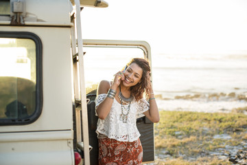 Smiling woman talking on mobile phone by off-road vehicle at beach