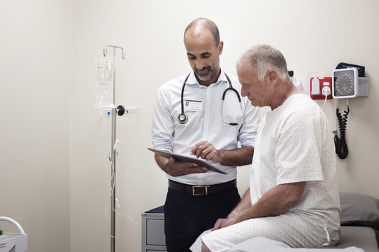 Doctor using digital tablet while standing by the patient