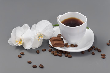 Orchid and white cup of coffee on a gray background